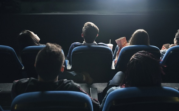 Rear view of the spectators in their seats watching movie at the cinema