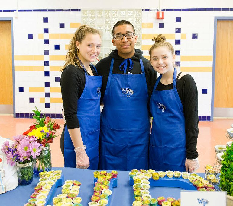 Student participants standing by their winning competition entry